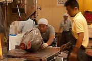 A worker saws a large tuna carcass in half at Tsukiji wholesale fish market in Tokyo, Japan  July 15th 2008