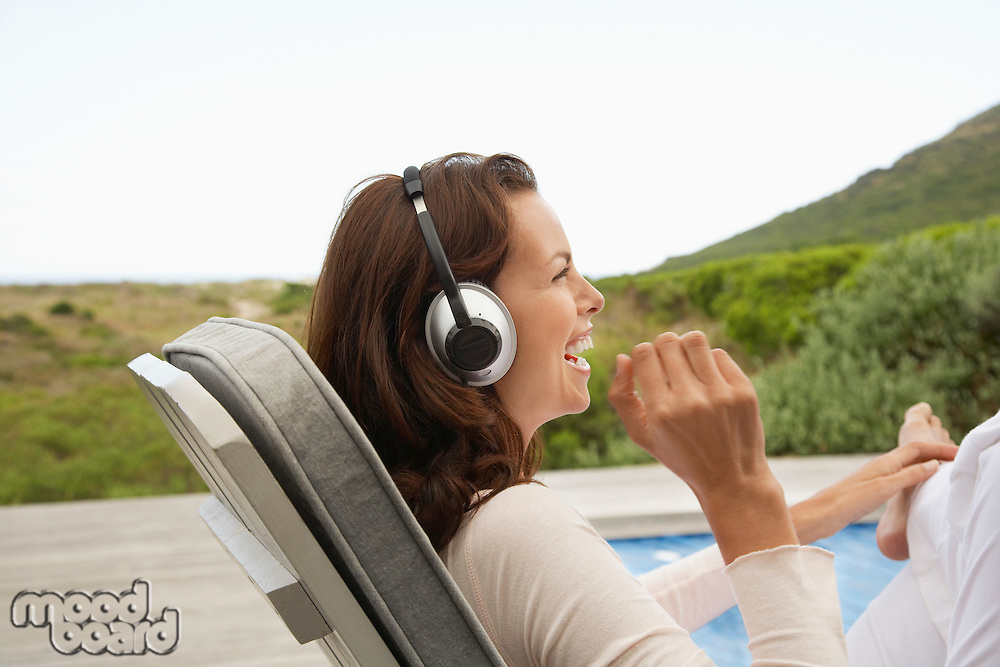 Woman wearing headphones laughing profile