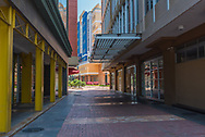 A walkway between tall buildings leads to a sunny plaza