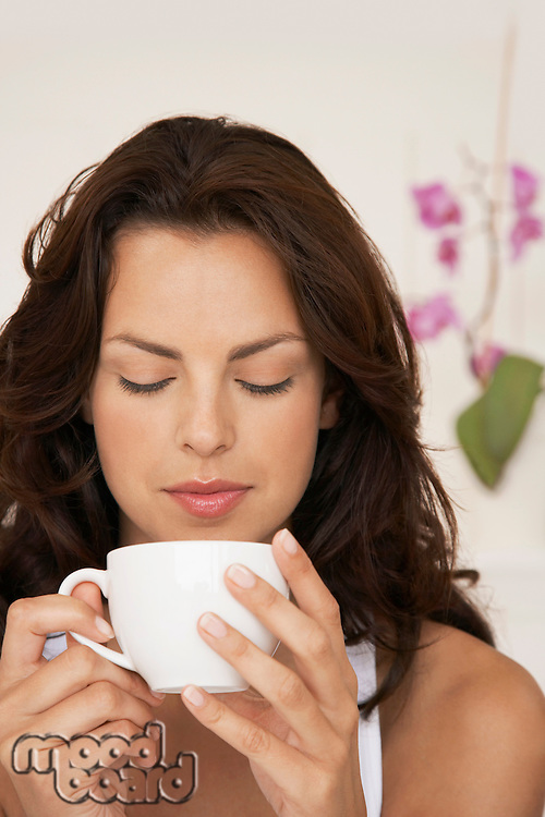 Woman drinking cup of tea head and shoulders