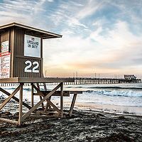 Photo of Newport Beach lifeguard tower 22 and Newport Pier at sunrise. Newport Pier is located on Balboa Peninsula in Orange County Southern California along the Pacific Ocean. Photo is high resolution HDR style.