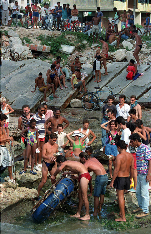 8/1994-Al Diaz/Miami Herald--In 1994 Cuban balseros left Cuba by the thousands seeking a better life. Here, a raft washes ashore in Havana and is stripped for it's inner tubes.