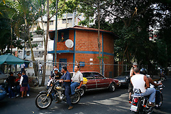 Motorcycles drive by one of the many clinics in Caracas where people can receive free health care from Cuban doctors. The doctors work in Venezuela as part of the doctors for oil deal setup between Cuba and Venezuela.