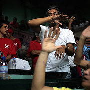THE PHILIPPINES (Manila). 2009. Gamblers make wagers with each other as they bet on the cockfighting at the Pasay Cockpit Arena,  Pasay City, Manila. Photo Tim Clayton <br /> <br /> Cockfighting, or Sabong as it is know in the Philippines is big business, a multi billion dollar industry, overshadowing Basketball as the number one sport in the country. It is estimated over 5 million Roosters will fight in the smalltime pits and full-blown arenas in a calendar year. TV stations are devoted to the sport where fights can be seen every night of the week while The Philippine economy benefits by more than $1 billion a year from breeding farms employment, selling feed and drugs and of course betting on the fights...As one of the worlds oldest spectator sports dating back 6000 years in Persia (now Iran) and first mentioned in fourth century Greek Texts. It is still practiced in many countries today, particularly in south and Central America and parts of Asia. Cockfighting is now illegal in the USA after Louisiana becoming the final state to outlaw cockfighting in August this year. This has led to an influx of American breeders into the Philippines with these breeders supplying most of the best fighting cocks, with prices for quality blood lines selling from PHP 8000 pesos (US $160) to as high as PHP 120,000 Pesos (US $2400)..