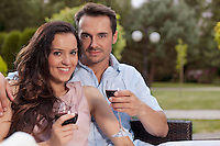 Portrait of beautiful young couple having red wine in park