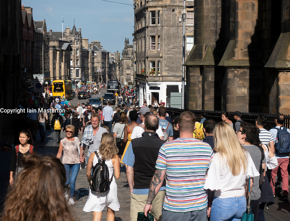 Many tourists walking in sunshine on the Royal Mile in Edinburgh Old Town, Scotland, UK