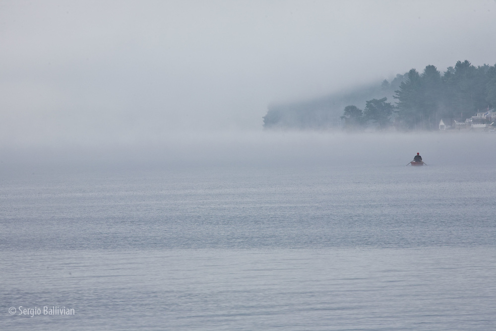 People are paddling boats early in the morning as fog rises on Lake Sebago in Maine