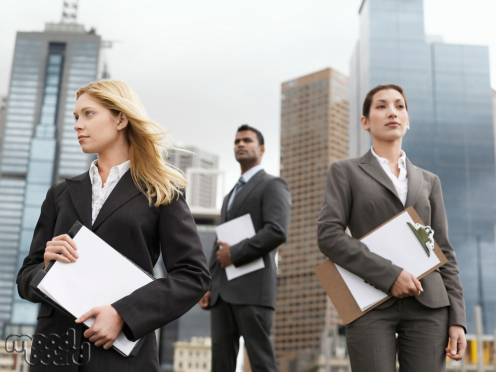 Three business people with clipboards outside office buildings