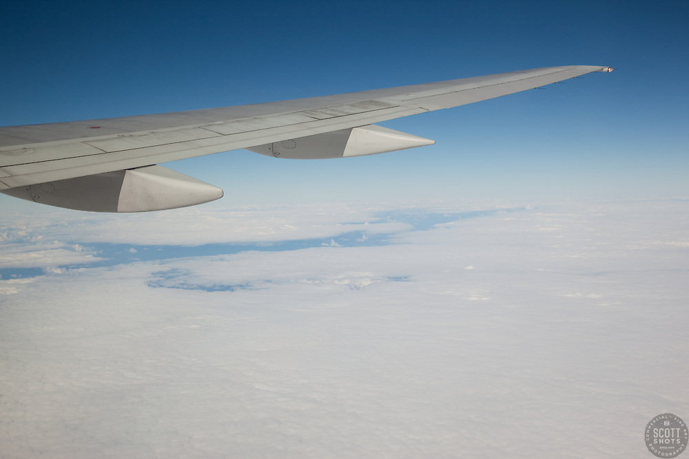 Aerial photograph from an airplane with wing and clouds.