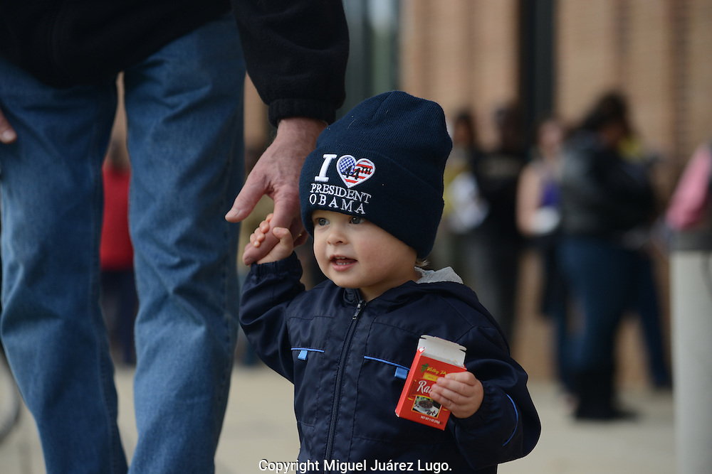 CHARLOTTE, NC - NOV 03, 2012.- A future voter shows his true colors held by the hand of his grandfather, while real voters queue to cast  their vote at a station that accepts early vote. In this swing state,  Mitt Romney maintains a slight edge on Obama, but the results are subject to citizen participation. (Photo by Miguel Juárez Lugo)