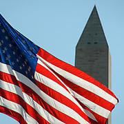 USA Flag and Washington Monument. The American flag, backlit, in the foreground, with the top of the Washington Monument in the background.