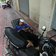 A decade ago Vietnams roads were teaming with bicycles. But as the countries economic growth increased bringing relative affluence to the working class, the push bike has been replaced by the scooter as the main mode of transport for the nations population.. Ho Chi Minh City alone has an estimated three million scooters buzzing around the streets day and night. Everyday life is dominated by the site of the scooter. Street corners have become parking lots for rows upon rows of parked scooters.. Puncture repair workmen wait on every city street to come to the aid of the rider with a blown tyre, and make a quick buck in the process, while families have a night on the town together, all seated on the same scooter!.Any number of items can be seen transported on the back of a scooter, from pigs to wardrobes anything that can be tied down is moved on the trusted scooter..Even in the outlying country areas the scooter is now used to transport produce to and from the markets. While even beach goers at the coastal towns head for a swim and a sunbathe accompanied by their scooter. .Street Scene, Ho Chi Minh City, Vietnam on September 29, 2006. Photo Tim Clayton