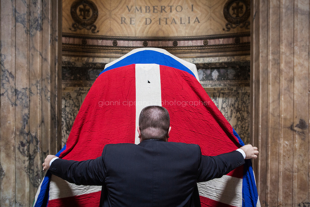 ROME, ITALY - 29 JULY 2014: Alberto di Maria (29), an event organizer and Honor Guard to the royal tombs of the Pantheon,  covers the tomb of Umberto I (King of Italy from 1878 until his death on July 29th 1900) with the flag of the Kingdom of Italy before  a mass to commemorate the anniversary of his death, in Rome, Italy, on July 29th 2014.<br /> <br /> The National Institute for the Honor Guards to the royal tombs of the Pantheon is a monarchic-oriented whose goal is to watch over the royal tombs at the Pantheon. Italy&rsquo;s first king, Vittorio Emanuele II and his son Umberto I, as well as Umberto's wife Queen Margherita are entombed in the Pantheon.