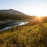 A hiker takes in the sunrise over the campgroud at Summit Lake, in Stone Mountain Provincial Park, Northern Rockies, British Columbia