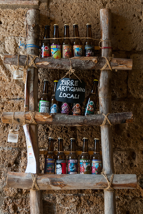 A display of craft beer in the streets of the village of Civita di Bagnoregio.<br /> Civita di Bagnoregio is a town in the Province of Viterbo in central Italy, a suburb of the comune of Bagnoregio, 1 kilometre (0.6 mi) east from it. It is about 120 kilometres (75 mi) north of Rome. Civita was founded by Etruscans more than 2,500 years ago. Bagnoregio continues as a small but prosperous town, while Civita became known in Italian as La citt&agrave; che muore (&quot;The Dying Town&quot;). Civita has only recently been experiencing a tourist revival. The population today varies from about 7 people in winter to more than 100 in summer.The town was placed on the World Monuments Fund's 2006 Watch List of the 100 Most Endangered Sites, because of threats it faces from erosion and unregulated tourism.