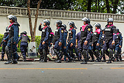 07 AUGUST 2013 - BANGKOK, THAILAND: Thai riot police leave their duty stations after being relieved when protesters trying to reach the parliament building in Bangkok ended their protest. About 2,500 protestors opposed to an amnesty bill proposed by Thailand's ruling party marched towards the Thai parliament in the morning. The amnesty could allow exiled fugitive former Prime Minister Thaksin Shinawatra to return to Thailand. Thaksin's supporters are in favor of the bill but Thai Yellow Shirts and government opponents are against the bill. Thai police deployed about more than 10,000 riot police and closed roads around the parliament. Although protest leaders called off the protest rather than confront police, a few people were arrested for assaulting police when they tried to break through police lines. Several police officers left the scene under medical care after they collapsed in the heat.    PHOTO BY JACK KURTZ