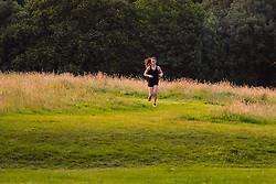 Hampstead Heath, London, July 20th 2016. A woman runs through Hampstead Heath as the first rays of the sun illuminate the grass as London prepares for another hot summer's day. ©Paul Davey<br /> FOR LICENCING CONTACT: Paul Davey +44 (0) 7966 016 296 paul@pauldaveycreative.co.uk