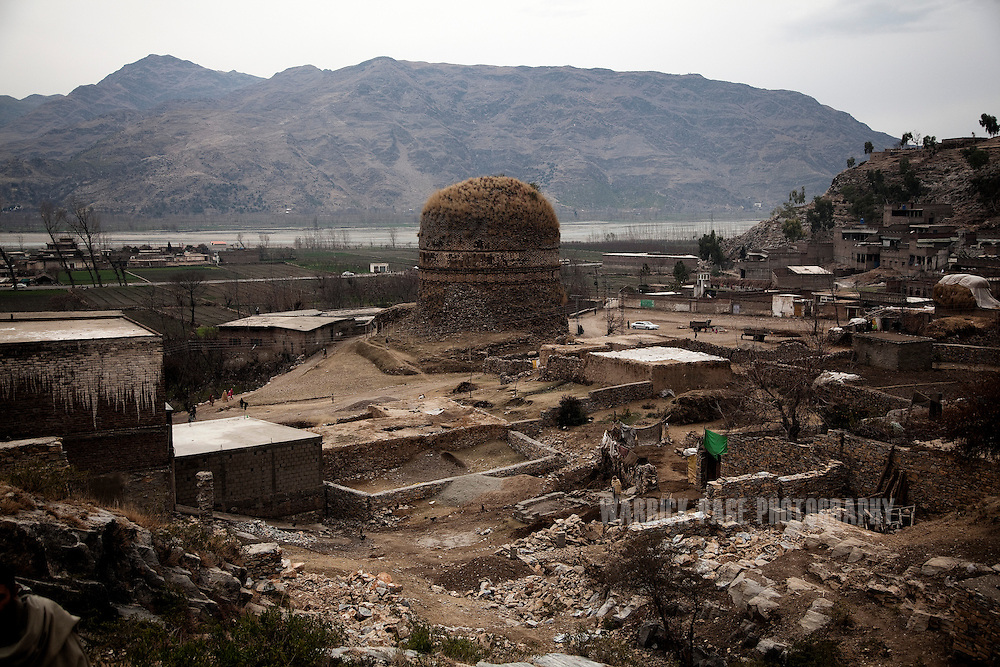 A village is seen surrounding the Shingardar Stupa in the Swat Valley, on February 11, 2011, in Gumbatuna, Pakistan. The Kingdom of Gandhara lasted from early 1st millennium BC to the 11th century AD, and was located in northern Pakistan and eastern Afghanistan. (Photo by Warrick Page)