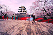 Hirosaki Japan. A photographer is seen photographing this wonderful castle. This year spring was early and so, not many tourists. A rare capture of the castle without hundreds of people on the bridge trying to get a good shot.<br /> Hirosaki Castle in Aomori Prefecture in Northern Honshu, Japan. Over 3,000 cherry trees come into bloom from mid April to early May.