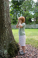 Girl (3-4) standing in front of tree covering eyes