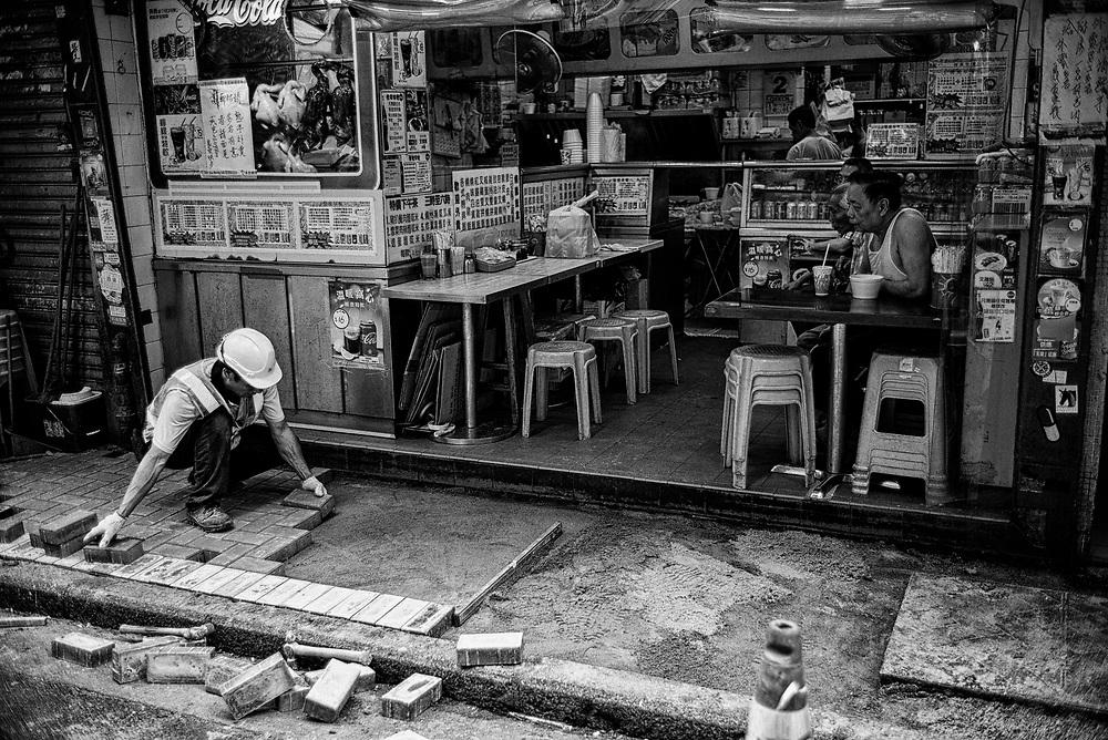 Hong Kong | 02.05.2017: Hong Kong <br /> <br /> hier: Ein Bauarbeiter pflstert den B&uuml;rgersteig vor einem Restaurant neu<br />  <br /> Sascha Rheker<br /> 20170502<br /> <br /> [Inhaltsveraendernde Manipulation des Fotos nur nach ausdruecklicher Genehmigung des Fotografen. Vereinbarungen ueber Abtretung von Persoenlichkeitsrechten/Model Release der abgebildeten Person/Personen liegt/liegen nicht vor.]