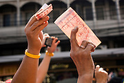 05 JANUARY 2014 - BANGKOK, THAILAND: People hold cash in the air before giving it to Suthep Thaugsuband during an anti-government march in Bangkok. Suthep, leader of the anti-government protests in Bangkok, led the protestors on a march through the Chinatown district of Bangkok. Tens of thousands of people waving Thai flags and blowing whistles gridlocked what was already one of the most congested parts of the city. The march was intended to be a warm up to their plan by protestors to completely shut down Bangkok starting Jan. 13.     PHOTO BY JACK KURTZ