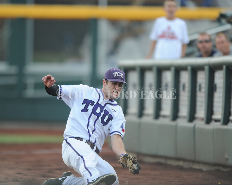 TCU's Dylan Fitzgerald (38) makes a sliding catch on a ball hit by Mississippi's Will Allen (30) in the College World Series at T.D. Ameritrade Park in Omaha, Neb. on Thursday, June 19, 2014. Ole Miss won 6-4.