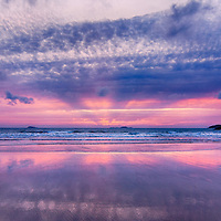 Purple and mauve sunset over sandy beach with dark hills