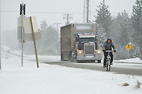 James Ledbetter rides his bike to work along Highway 53 during a snow flurry Thursday in Rathdrum.
