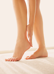 Woman Applying Body Lotion on Heel, Low Section