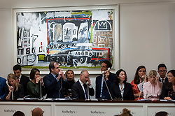 © Licensed to London News Pictures. 26/06/2018. LONDON, UK. Sotheby's staff making bids on behalf of telephone bidders in front of ''New York, New York'' by Jean-Michel Basquiat, (Est. £7,000,000 - 10,000,000) which sold for a hammer price of £7,000,000 at Sotheby's Contemporary art evening sale in New Bond Street.  Photo credit: Stephen Chung/LNP
