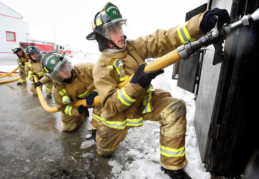 JEROME A. POLLOS/Press..Coeur d'Alene firefighters Adam Heaton, front, and Justin Wearne practice entry and attack procedures Monday during a training routine for five new firefighters hired by the city.