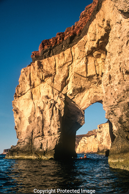 Kayaker paddling through a natural sea arch, Isla Partida, near La Paz, Sea of Cortez and the Baja Peninsula, Mexico.<br />