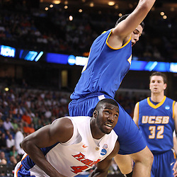 Mar 17, 2011; Tampa, FL, USA; Florida Gators forward/center Patric Young (4) is fouled by UC Santa Barbara Gauchos forward Jaime Serna (0) during first half of the second round of the 2011 NCAA men's basketball tournament at the St. Pete Times Forum.  Mandatory Credit: Derick E. Hingle
