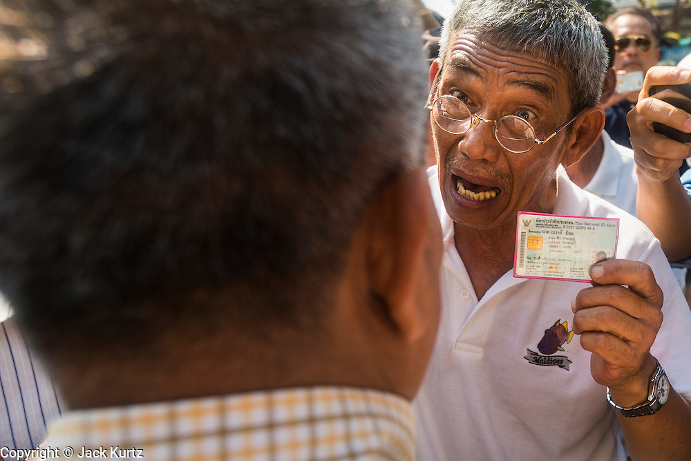 "01 FEBRUARY 2014 - BANGKOK, THAILAND: A Thai voter confronts an election worker with his ID card. The man was told he couldn't vote because protestors had blocked the polls. Thais went to the polls in a ""snap election"" Sunday called in December after Prime Minister Yingluck Shinawatra dissolved the parliament in the face of large anti-government protests in Bangkok. The anti-government opposition, led by the People's Democratic Reform Committee (PDRC), called for a boycott of the election and threatened to disrupt voting. Many polling places in Bangkok were closed by protestors who blocked access to the polls or distribution of ballots. The result of the election are likely to be contested in the Thai Constitutional Court and may be invalidated because there won't be quorum in the Thai parliament.    PHOTO BY JACK KURTZ"
