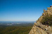 A hiker triumphantly stands a top the cliff he has conquered, far above the trees, hills, and human life below.