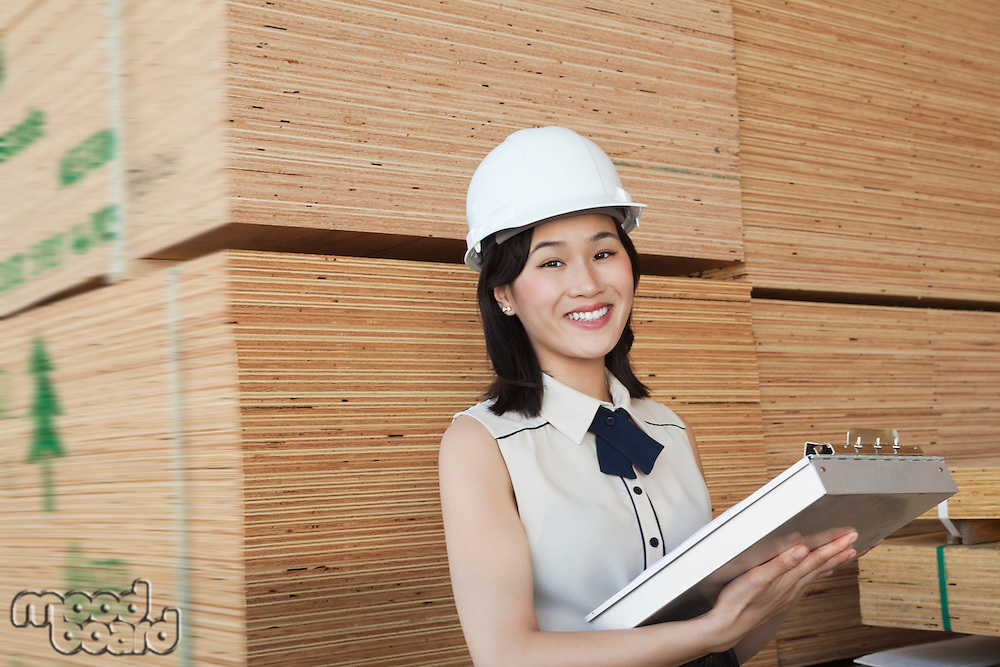 Portrait of female industrial worker holding clipboard with stacked wooden planks in background