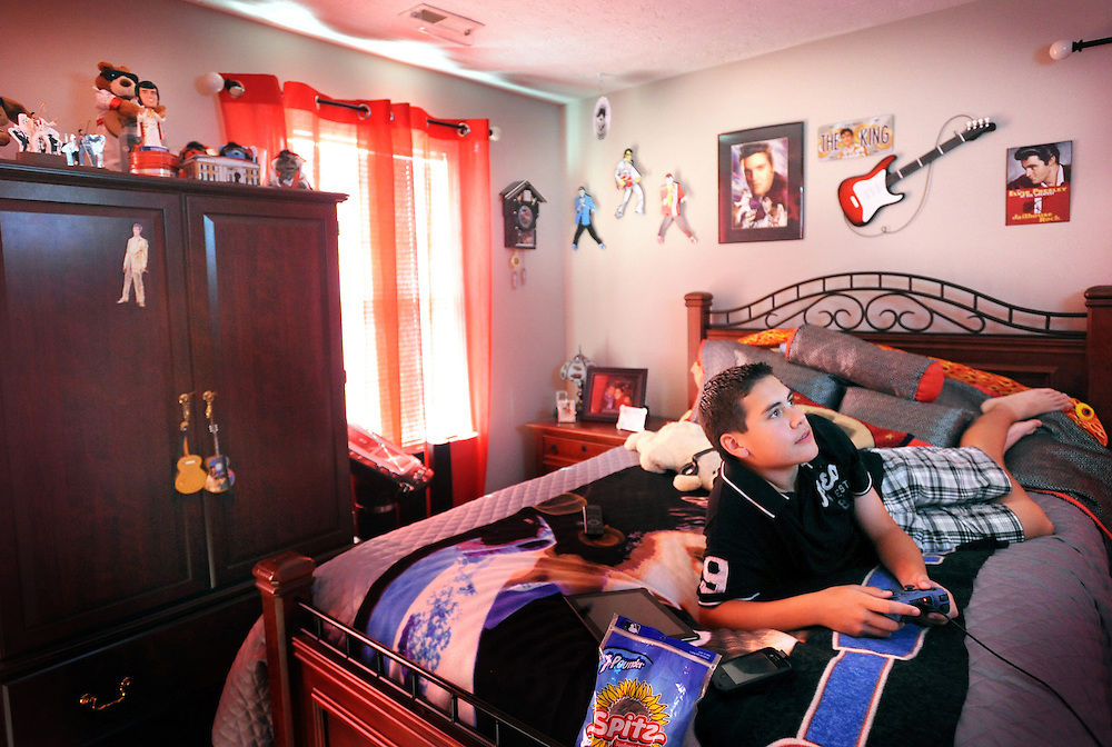 At home in his Elvis themed bedroom in Goode, Taylor Rodriguez plays video games.  Rodriguez has been collecting Elvis memorabilia since his late aunt game him his some items when he was young.