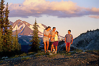 Family laughs with each other during an evening hike on Whistler Mountain, BC, Canada.
