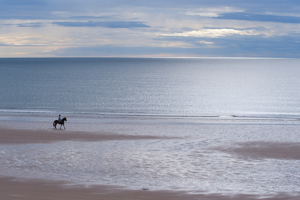 Woman on horseback at the edge of the North Sea, Scotland