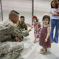 Chief Warrant Officer Four Jamie White, left, gets a handshake slap from Saydie Kirby, 4, before her father, Sgt. Branden Kirby, second from left, gets deployed to the border with mexico in the coming weeks as part of Company C 1-114th Aviation Security and Support.