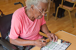 Elderly visually impaired woman playing bingo