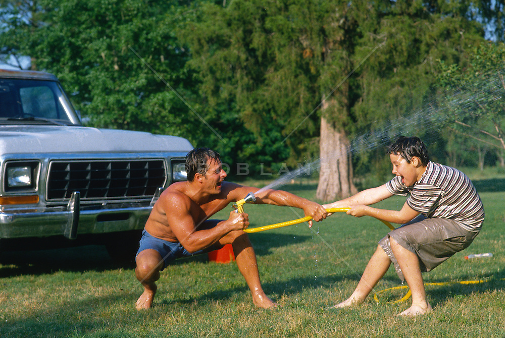 Man Spraying water from a garden hose at a boy