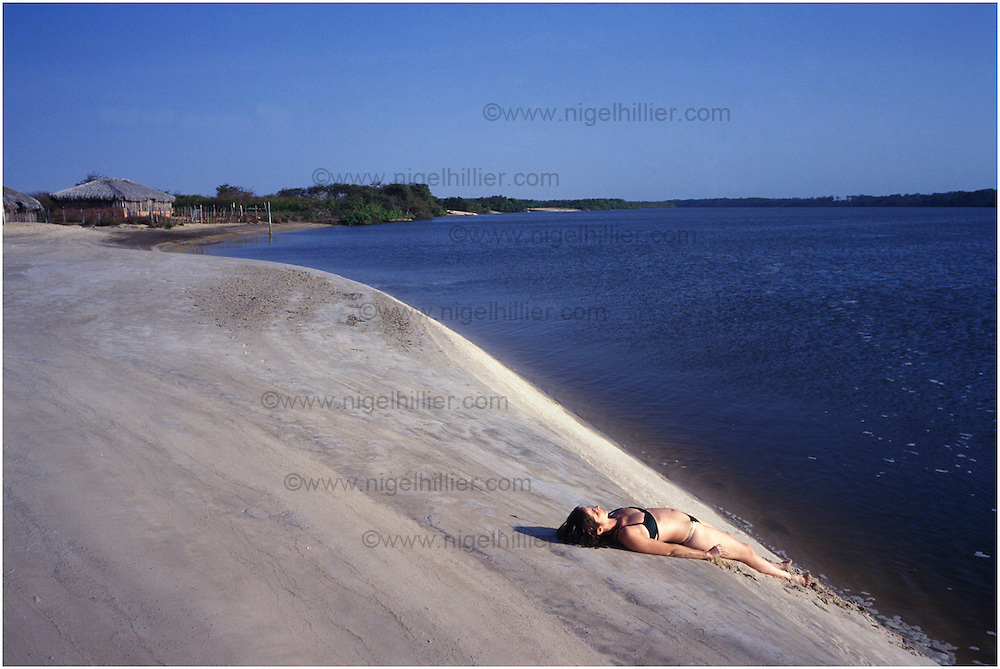 copyright: Nigel Hillier.Brazil, Maranhao, Parque National Dos Lencois, Maranhenses, Cabure village .girl lying on river beach