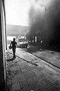 198 / G8-Gipfel in Genua 2001: EUROPA, ITA, ITALIEN, GENUA, LIGURIEN,18. bis  22. Juli 2001: Ein vermummter Demonstrant laeuft an einer brennenden Bank vorbei. Der G8-Gipfel in Genua war ein Treffen der Gruppe der Acht in der italienischen Stadt Genua. Der insgesamt 27. G8-Gipfel fand vom 18. bis zum 22. Juli 2001 statt. Er wurde von schweren Auseinandersetzungen zwischen der italienischen Polizei und Globalisierungskritikern, bei denen Carlo Giuliani von einem Polizisten erschossen und hunderte Personen verletzt wurden, ueberschattet. Die juristische Aufarbeitung dauert bis heute an.--- The Genoa Group of Eight Summit protest, from July 18 to July 22, 2001, was a dramatic protest, drawing an estimated 200,000 demonstrators. Dozens were hospitalized following clashes with police and night raids by security forces on two schools housing activists and independent journalists. People taken into custody after the raids have alleged severe abuse at the hands of police. - Marco del Pra / imagetrust - Stichworte: Anarchie, anarchy, Autonome, autonomi, black, Black Block, block, carlo giuliani, Civil Rights, clash, clashes, Demonstrant, Demonstranten, demonstration, demonstrator, demonstrators, demonstrieren, disobbedienti, disobedience, G8, G8 Gipfel, G8Gipfel, Gegner, genoa, genova, Genua, Gewalt, Gipfelgegner, Global, Globalisation, Globalisierung, Italien, italy, Krawall, Krawalle, Kritiker, Menschenrechte, Neoliberal, Neoliberalisums, No Global, police, Politics, Politik, Polizei, protest, protester, riot, Schwarz, summit, Treffen, violence, Weiss, Weltwirtschaft, Weltwirtschaftsgipfel, Wirtschaft, Wirtschaftsgipfel, Feuer, Bank, Brennen, Architektur, Rauch, vermummt, helm, strassenschlacht,