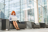 Full-length of middle-aged businesswoman using laptop at office lobby