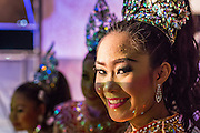22 NOVEMBER 2013 - BANGKOK, THAILAND: Performers with the Prathom Bunteung Silp mor lam troupe wait in the wings to go onstage during a performance in Bangkok. Mor Lam is a traditional Lao form of song in Laos and Isan (northeast Thailand). It is sometimes compared to American country music, song usually revolve around unrequited love, mor lam and the complexities of rural life. Mor Lam shows are an important part of festivals and fairs in rural Thailand. Mor lam has become very popular in Isan migrant communities in Bangkok. Once performed by bands and singers, live performances are now spectacles, involving several singers, a dance troupe and comedians. The dancers (or hang khreuang) in particular often wear fancy costumes, and singers go through several costume changes in the course of a performance. Prathom Bunteung Silp is one of the best known Mor Lam troupes in Thailand with more than 250 performers and a total crew of almost 300 people. The troupe has been performing for more 55 years. It forms every August and performs through June then breaks for the rainy season.       PHOTO BY JACK KURTZ