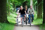 In Soest neemt een vader een kinder mountainbike mee aan de hand tijdens een fietstocht met het gezin.<br /> <br /> In Soest a father is cycling with the child's mountainbike on his hand during a cycling tour.