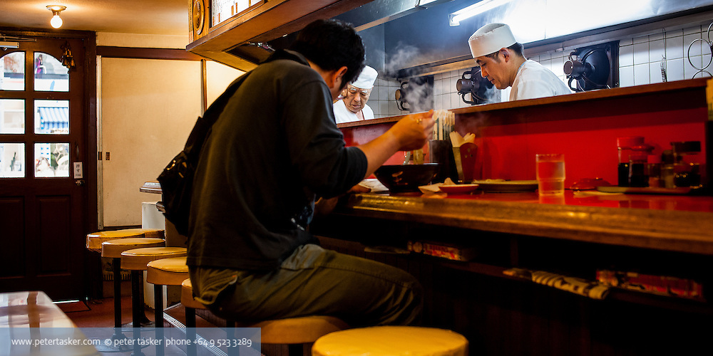 A man eating at a restaurant counter with two Japanese chefs behind.  Naha, Okinawa, Japan.