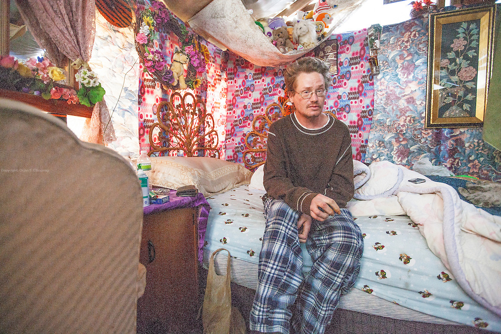"Up until 2014, Lakewood Tent City was home to some twenty people who otherwise would be homeless.<br /> In July 2014 the residents were forcefully evicted and the makeshift tents and huts demolished. Elwood (pictured) took pride in his ""gingerbread house"" made out of tarp and colorful fabrics. After the eviction he was moved to a temporary housing, where he struggles to cope."